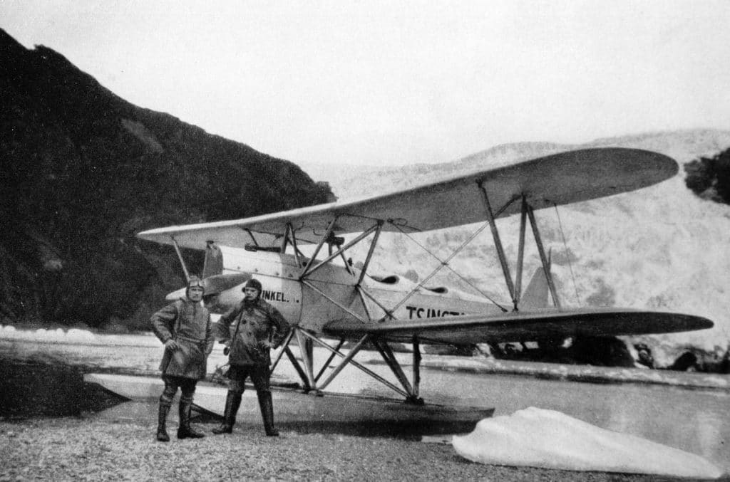 schwarz-weiß Bild von Filmmaterial aus den späten 1920ern: Zwei Männer vor einem Flugzeug