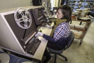 Ulirke Schmidt, Inhaberin von Film-Digital sitzt in der Lagerhalle bei der TIB am Filmprüftisch (RTI Pulsar 2800 TT) und sichtet einen Film.